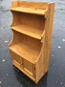 An Ercol oak whatnot cabinet with shaped sides and open shelves above panelled cupboards, with