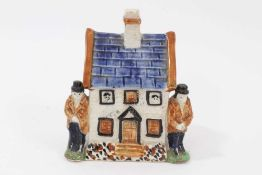 Early 19th century Staffordshire Prattware money box, modelled as a house with figures on either sid