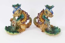 Pair of Cantagalli maiolica candlesticks, in the form of heraldic dragons with scallop shell bowls,