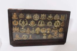 Group of First World War Military cap badges mounted in a glazed frame