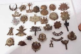 Group of First World War and later military cap badges, two silver war badges and various military a