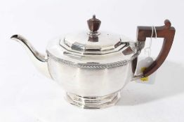 George V silver teapot of cauldron form with faceted decoration, bakelite finial and angular handle