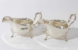 Pair of Edwardian silver sauce boats of conventional form with scroll handles, each raised on three