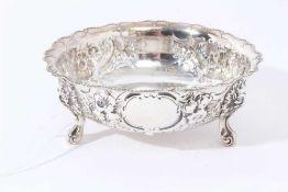 Victorian silver sugar bowl of circular form with foliate embossed borders, on three scroll feet ( L