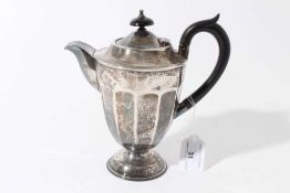 George V silver hot water jug of tapered form with faceted decoration, ebony finial and loop handle,