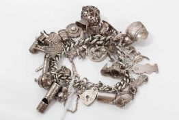 Silver charm bracelet with a collection of silver and white metal charm and padlock clasp.