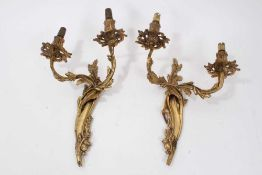 Pair of Rococo style gilt metal wall sconces, each scrolling foliate bracket issuing twin arms, 31cm