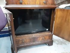 Samsung flatscreen television contained in a mahogany television cabinet