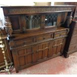 """A 4' 6"""" 20th Century polished oak court cupboard with leaded glazed panel doors and flanking"""