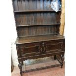 A 4' early 20th Century stained oak two part dresser with two shelf open plate rack over a base with