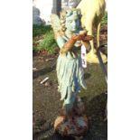 A painted cast iron garden fairy stood holding a bird