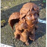 A cast iron garden angel with rusted finish