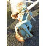 A painted cast iron garden cherub sat weeping on a finial