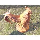 A cast iron garden cockerel with rusted finish