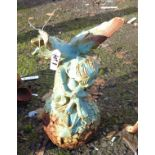A painted cast iron garden fairy sat weeping on a ball of flowers