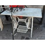 A Singer sewing machine table base with marble top and white painted finish