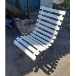 A slatted garden chair with wrought iron frame