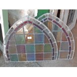 Two stained and leaded glass window panels with arched tops - some damage