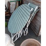 A wrought iron and wooden folding garden table and two chairs