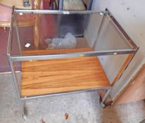 A 63cm vintage Howard Miller Ltd. Mda Product chrome framed two tier tea trolley with glass top