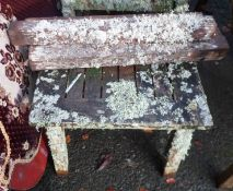 A Barlow Tyrie small teak coffee table covered in lichen