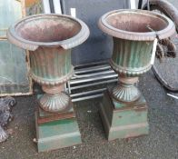 A pair of cast iron urns - some damage