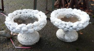 A pair of small concrete planters with floral decoration