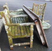 A Barlow Tyrie teak table and four chairs covered in lichen