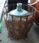 A large glass carboy with original straw filled iron cage