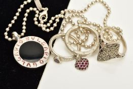 A WHITE METAL PENDANT NECKLACE AND THREE RINGS, the pendant of circular design, black enamel,