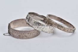 THREE SILVER HINGED BANGLES, the first a wide bangle with a foliate engrave design, push pin clasp