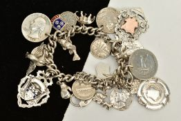 A SILVER CHARM BRACELET, suspending twenty-three charms, such as coins, fobs, a dog, crocodile,