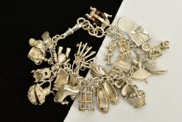 A CHARM BRACELET, suspending twenty five charms in forms such as a bird in a cage, ballerina
