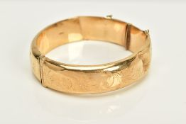 A 9CT GOLD HINGED OVAL BANGLE, half engraved (a.f. this bangle is damaged in several places)