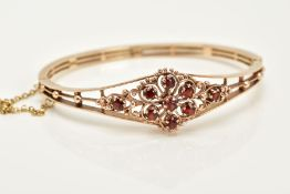 A 9CT GOLD GARNET SET OPENWORK BANGLE, the openwork hinged bangle of floral design, set with