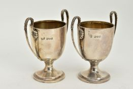 A PAIR OF SILVER DOUBLE HANDLED CUPS, of plain polished design, foliate detailed handles, upon a