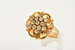 A YELLOW METAL CLUSTER RING, in the form of an openwork flower, set with circular cut colourless