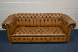 A TAN LEATHER BUTTONED CHESTERFIELD SOFA, along with later cushions, width 205cm