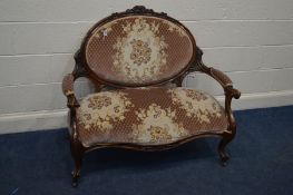 A VICTORIAN WALNUT TWO SEATER SOFA, with foliate decoration, oval back to swept open and scrolled