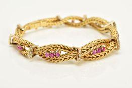 A MODERN YELLOW METAL DIAMOND AND RUBY BRACELET, designed as a twisted box chain bracelet, seven