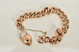 A YELLOW METAL CHARM BRACELET, a hollow curb link bracelet fitted with a heart clasp set with two