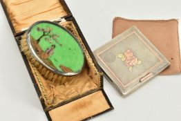 A CASED SILVER BRUSH AND WHITE METAL COMPACT, the small oval brush with a decorated green panel top,
