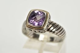 A SILVER AMETHYST RING, designed with a cushion cut amethyst within a collet mount with a rope twist