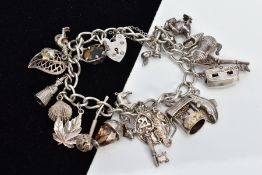 A SILVER CHARM BRACELET, suspending twenty white metal charms, such as a caravan which opens to