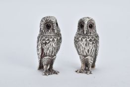 A PAIR OF SILVER SALT AND PEPPER POTS, each in the form of an owl, realistically modelled standing