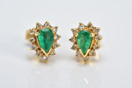 A PAIR OF YELLOW METAL, EMERALD AND DIAMOND CLUSTER EARRINGS, each designed with a central claw set,