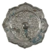 A Chinese silvered bronze octafoil mirror of lighua type, Tang dynasty, finely cast with five floral