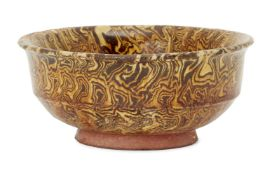 A Chinese marbled-pottery bowl, Tang dynasty, with steep straight sides to flared rim, covered in