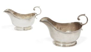A pair of silver sauce boats, London, c.1925, Asprey & Co., the plain body of each raised on an oval