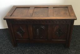 A carved oak three panelled coffer